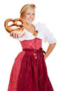 Happy woman offering pretzel bavarian in a dirndl a fresh Royalty Free Stock Photo