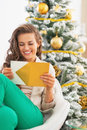 Happy woman opening christmas letter in front of christmas tree young Stock Photos