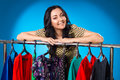 Happy Woman Over The Clothing Rack With Dresses