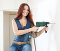 Happy woman in overalls with drill on stepladder the interior Stock Photos