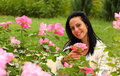 Happy woman in a park smiling rose garden holding rose blossom outdor Stock Photos