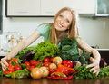Happy woman with pile of vegetables in kitchen Royalty Free Stock Images