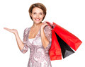 Happy woman with presentation gesture and shopping bags portrait of a beautiful over white background Stock Image