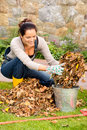 Happy woman putting dry leaves bucket yard autumn backyard cleaning garden Stock Photos
