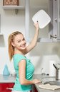 Happy woman putting plate to kitchen cabinet Royalty Free Stock Photo