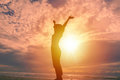 Happy woman raising hands up and beautiful sunrise in background Royalty Free Stock Photo