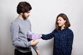 A happy woman receiving a present from her boyfriend. A stylish boy dressed in casual sweater giving her girlfriend a present for Royalty Free Stock Photo