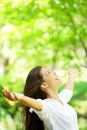 Happy woman rejoice looking up happy enjoying spring or summer forest park smiling with arms outstretched beautiful mixed race Royalty Free Stock Image