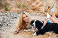 Happy woman relaxing with dog on the beach Royalty Free Stock Photo