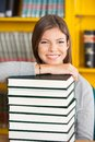 Happy woman resting chin on stacked books in portrait of young college library Royalty Free Stock Image