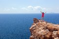 Happy woman on the rock with hands up. Winner, success, travel. Royalty Free Stock Photo