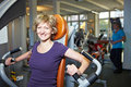 Happy woman on rowing machine Royalty Free Stock Image