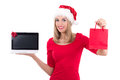 Happy woman in santa hat holding notebook and present over white background Royalty Free Stock Images