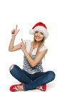 Happy woman in Santa hat pointing up Stock Photo