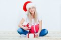 Happy woman in santa hat sitting on carpet Stock Photography