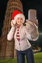 Happy woman in Santa hat taking selfie near Leaning Tower, Pisa Royalty Free Stock Photo