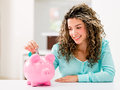 Happy woman saving money in a piggybank Royalty Free Stock Photo