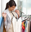 Happy woman selecting clothes whole at the mall Stock Photography