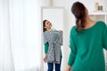 Happy woman with shirt looking to mirror at home Royalty Free Stock Photo
