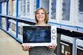 Happy woman shopper buys microwave in store Royalty Free Stock Photo
