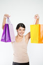 Happy woman shopper with colorful bags full of her recent purchases turning to smile at the camera a look of satisfaction and Stock Images