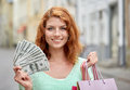 Happy woman with shopping bags and money on street Royalty Free Stock Photo