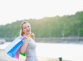 Happy woman with shopping bags walking quay Stock Image