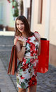 Happy woman with shopping bags young smiling in a small street of an old city Royalty Free Stock Photo