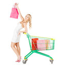 Happy woman with shopping cart and bags retail sale concept Stock Images