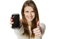 Happy woman showing her mobile phone and gesturing thumb up Royalty Free Stock Photo