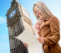 Happy woman sightseeing london holding map smiling Stock Photo