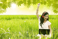 Happy woman singing in field is green while holding a laptop Royalty Free Stock Photos