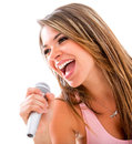 Happy woman singing with a microphone isolated over a white background Stock Photo
