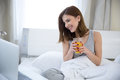 Happy woman sitting on the bed with juice and looking laptop Stock Photos
