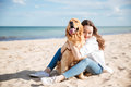 Happy woman sitting and hugging her dog on the beach Royalty Free Stock Photo