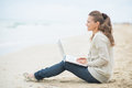 Happy woman sitting with laptop on cold beach young Stock Image