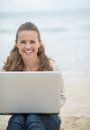 Happy woman sitting with laptop on cold beach young Stock Photo