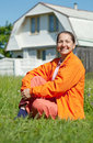 Happy woman sitting on lawn in front of  home Royalty Free Stock Photos