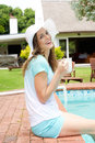 Happy woman sitting poolside with cup of coffee Royalty Free Stock Photo