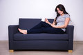 Happy woman sitting on sofa with phone and mug of tea or coffee Royalty Free Stock Photo