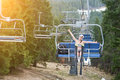 Cute naked female skier is having fun on ski lift and riding up to the top of the mountain with   helmet