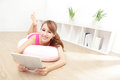 Happy woman smiles using tablet pc and looking to you at home asian beauty model Stock Image