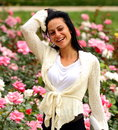 Happy woman smiling in a rose garden outdoor Stock Image