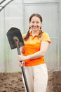 Happy woman with spade mature in hothouse Stock Photography