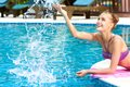 Happy woman splashing water in pool Royalty Free Stock Image