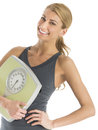 Happy woman in sports clothing holding weight scale portrait of young isolated over white background Stock Photos