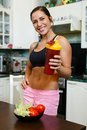 Happy woman with sports nutrition the young a protein cocktail in a shaker stands in house kitchen Stock Photos
