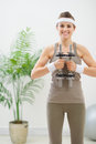 Happy woman in sportswear holding dumbbells Stock Photos