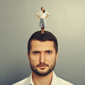 Happy woman standing on the displeased man small women head of Stock Photo