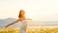Happy woman standing with her back on sunset in nature iwith ope Royalty Free Stock Photo